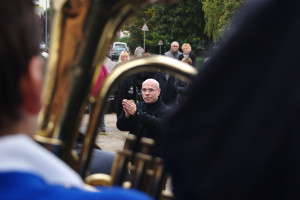 Director Pierre Boesplug through a Godalming Band horn
