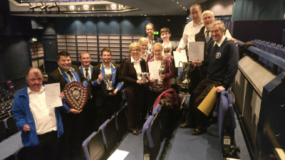Celebrating in the theatre with trophies from the B section win